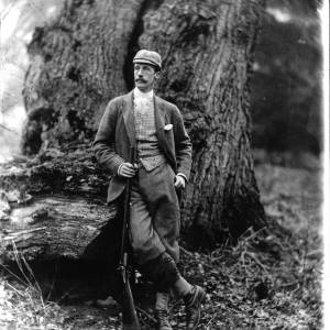 G36-259-01 Sporting gentlemen leans against tree with rifle in check jacket and matching hat.jpg