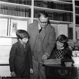 Lord Croft and two children looking at a book.
