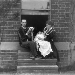 G36-235-01 Man with dog and lady with baby seated on steps.jpg