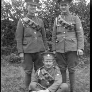 Two soldiers standing and one sitting by hedge