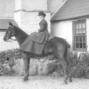 A lady on a horse in the grounds of a large house.