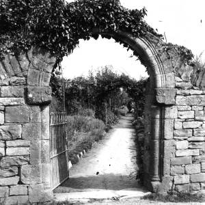G36-326-01 View of garden through an ivy covered stone archway.jpg