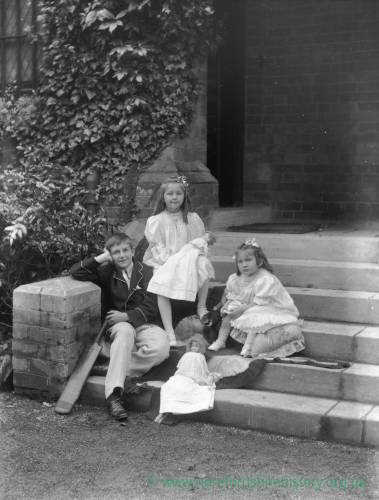 G36-221-09 Boy [as in G36-221-07] with two young girls and dolls, outside large house.jpg