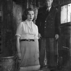 130 - John Mills and a woman in a wooden hut