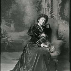 G36-213-03 Seated lady in velvet dress with full sleeves, jewellery, holding a long haired terrier.jpg
