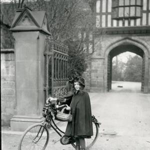 G36-025-01 Girl with cycle wearing cape and hood carrying basket of eggs. Outside Bishops Palace.jpg