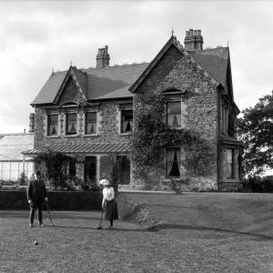 G36-355-09 Man and young  lady playing croquet on lawn in front of large house .jpg
