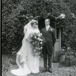 G36-024-10 Bride and groom standing in front of creeper covered doorway.jpg