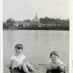RGE006 - Two young boys playing in the river with a view of the town and church.jpg