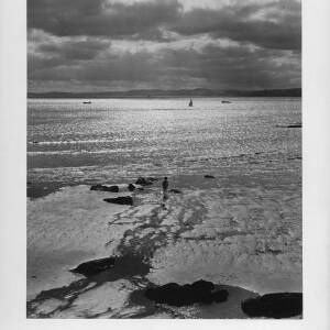 611 - Sunlight on sea, young boy on shore