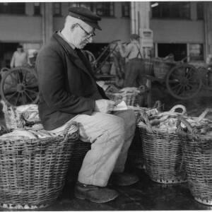 658 - Man sitting on fish basket and writing