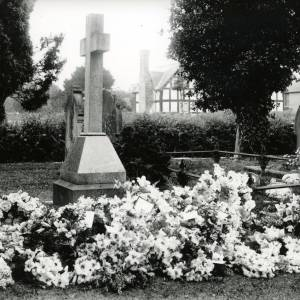 G36-004-02 Graveyard with floral tributes. Black and white house beyond.jpg