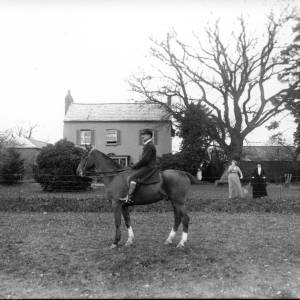 G36-304-04 Man seated on hunter in front of house with two ladies.jpg