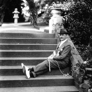 G36-328-06 Man with monkey seated on stone steps.jpg
