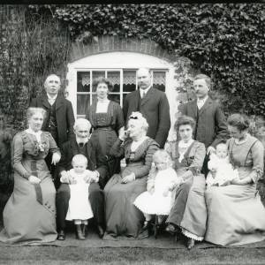 G36-028-11 Family group in front of window in creeper covered wall. Grandparents and two generations. two toddlers and baby.jpg
