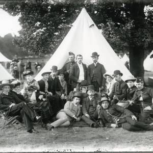 G36-028-04  Group of 7 civilian men, 3 soldiers, 6 ladies in front of tent on parkland. Tents and civilians in background.jpg