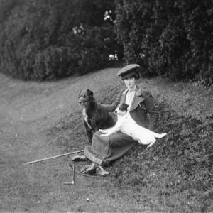 G36-246-11 Same lady as plate G36-246-01 et seq, seated on grassy bank with 2 dogs.jpg