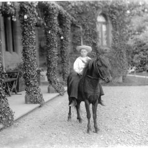 G36-057-03 Young boy as G36- 057-01 wearing a large straw hat, seated on pony in front of a house with ivy covered pillars.jpg