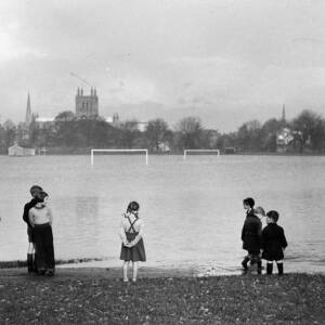 Young children standing near floodwater at Bishops Meadows, Hereford.