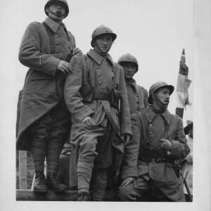 643 - Four soldiers wearing great coats & tin hats