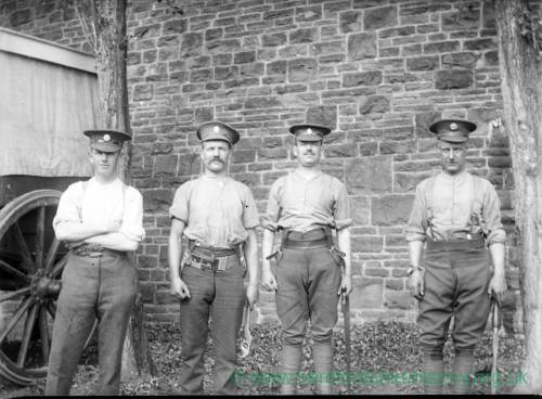Four soldiers standing in front of a wall and cart