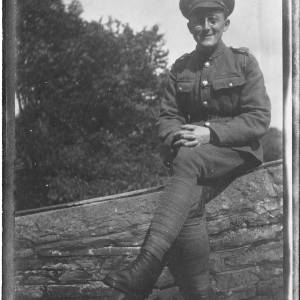 Soldier in uniform sitting on wall