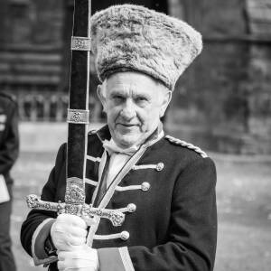 Man holding sheathed sword