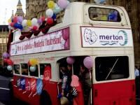 Open-top bus advertising Merton Council and Wimbledon Theatre