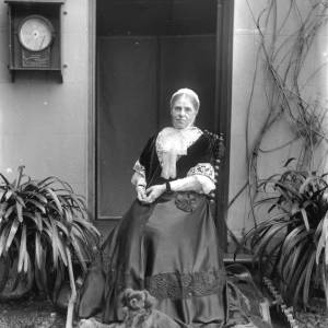 G36-222-01 Frances Leigh seated outside Deanery with Pekinese dog at her feet.  On the wall is a patent thermometer.jpg