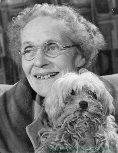 A smiling Margaret Hunter holding her pet dog.