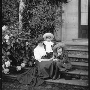 G36-032-12 Lady sitting on steps in front of French windows with a girl and boy. Box camera nearby. The children have large brimmed hats .jpg