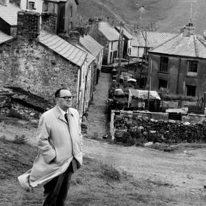 Man in front of a Welsh Mining town.