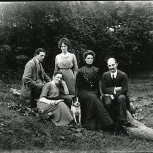 G36-205-07 Three ladies, 2 men & a dog on a log by a hedge.jpg