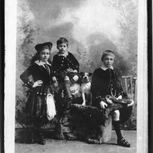 G36-108-01 Portrait of 3 children in Highland dress. Girl and 2 boys and Jack Russell terrier (copy negative), Hewatt family.jpg