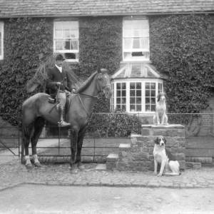 G36-251-07 Young man from G36-251-02, mounted on hunter outside the same house. 2 dogs beside him on mounting block.jpg