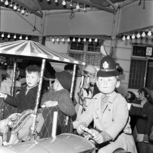 Little Boy in a Policeman's Helmet on a Ride at the Hereford May Fair in 1965