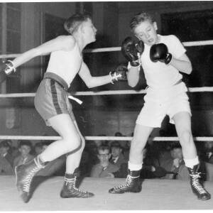 234 - Two youths boxing in ring, spectators in background