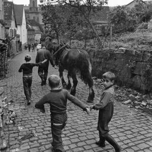021 - Man leading horse with three young boys
