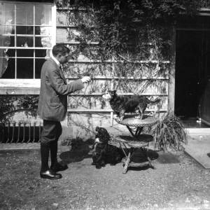 G36-543-01 Man standing outside a house, training two dogs.jpg