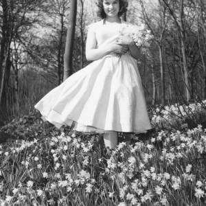 Lady in a pale dress picking daffodils