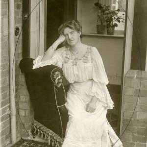G36-009-02 Portrait of same lady in a doorway seated on arm of a chair.jpg