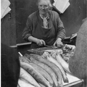 280 - Woman fileting fish; fish arranged on a slab in front of her