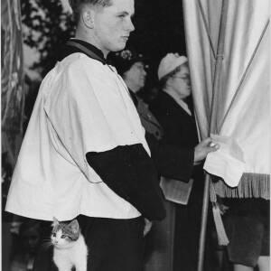 689 - Choir boy holding banner, kitten in his pocket