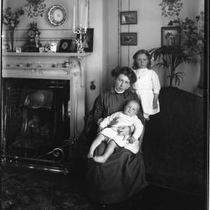 G36-033-09 Interior. Lady seated on settee with girl and baby. Posed at side of fireplace, the mantelpiece has various ornaments. The wallpaper is decorated with garlands and ribbons .jpg