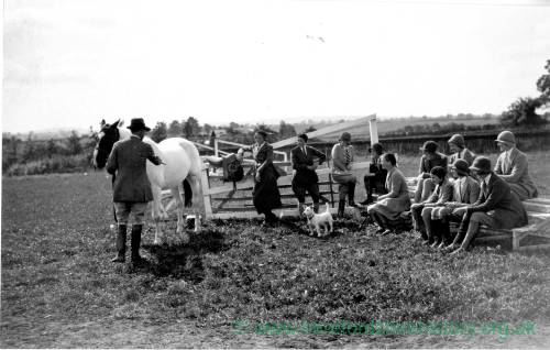 Man giving instruction on horses to a class in the fields, date unknown