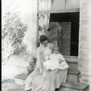 G36-026-17 Older woman with baby on steps outside open window.jpg