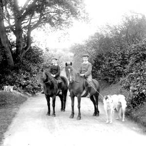 G36-244-13 Two young lads mounted on ponies in a country lane. One holds the lead of an Irish Wolf Hound.jpg