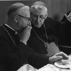 Two priests in conversation at the dining table.