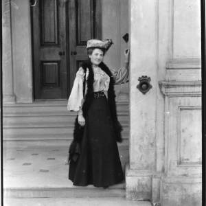 G36-035-01 Lady standing at entrance of building. Steps and door behind her. She is wearing a toque, feather boa  and a dark skirt with a light blouse.jpg