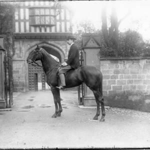 G36-034-02 Man wearing bowler hat on horse outside gate to Bishop's Palace.jpg